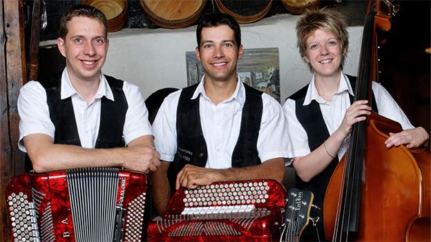 Zwei Musikanten und eine Musikantin vor ihren Instrumenten: zwei Akkordeons und ein Kontrabass.