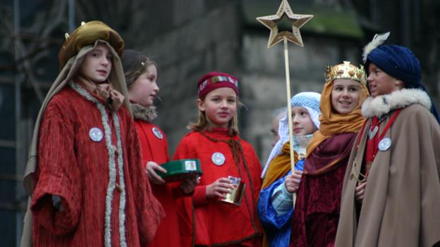 Sternsinger stehen vor Kirche in Kostümen der drei Könige.