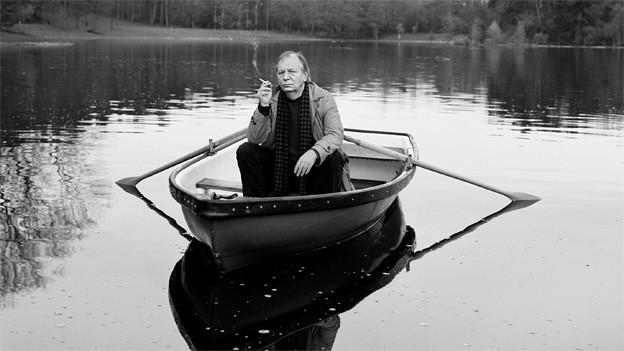 Schwarz-Weiss Fotografie mit dem Kabarettisten, der in einem Ruderboot auf dem See ist und eine Zigarette raucht.