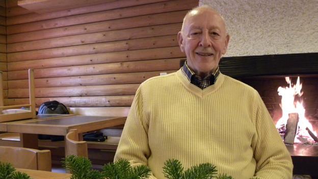 Der 83-jährige Rentner trägt einen gelben Pullover über einem karierten Hemd und sitzt vor einem Cheminée, in dem ein Feuer lodert.