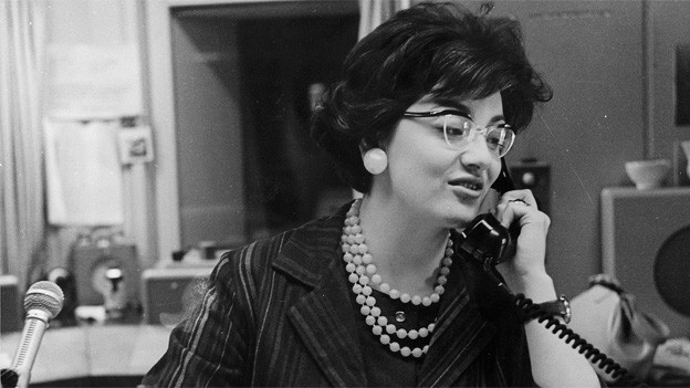 Schwarz-Weiss Fotografie von Elisabeth Schnell im Sendestudio. Die Moderatorin sitzt vor dem Mikrofon und telefoniert.