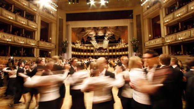 Opernball im Opernhaus Wien. Debutantenpärchen - er in schwarz, sie in weiss - wirbeln übers Tanzparkett. Die Pärchen sind nur unscharf zu sehen wegen der speziellen Kameraeinstellung.