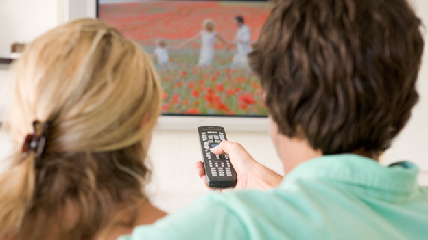 Ein junges Paar sitzt auf dem Sofa und schaut fern. Auf dem Bildschirm läuft gerade eine Werbespot, der eine junge Familie inmitten von Mohnblumen zeigt.