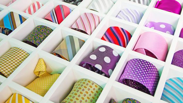 Bunte gerollte Krawatten sortiert in einer Schublade.