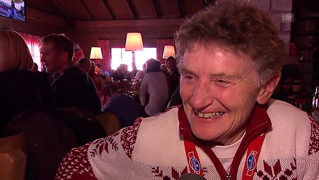 Die Seniorin steht in einer Skihütte und trägt einen rot-weissen Skipullover.