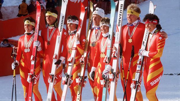 Die Athleten und Athletinnen posieren in grell farbenen Anzügen mit ihren Skiern für die Fotografen und zeigen ihre Medaillen.