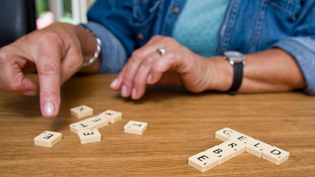 Frauenhände, die mit Scrabble-Buchstaben die Wörter Geld und Erbe legen.