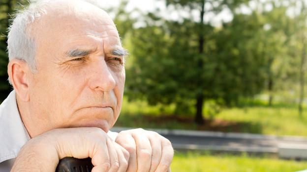 Ein älterer Mann mit grauen Haaren stützt sich nachdenklich auf seinen Stock.