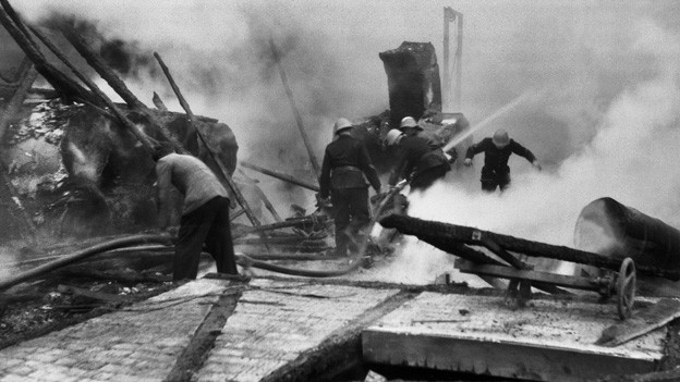 Historische Schwarz-Weiss Fotografie mit einer gespenstisch anmutenden Szene zwischen Bahnwaggons und Geleisen.