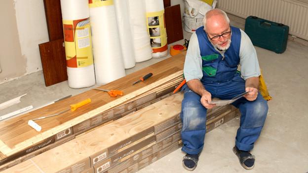 Ein Rentner studiert die Anleitung zum Verlegen eines Parkettbodens und sitzt auf einem Stapel mit langen Holzlatten.