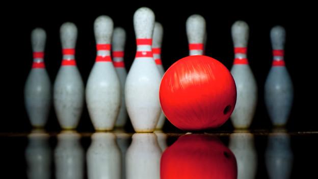 Eine Bowlingkugel vor neun Pins, die sich im schwarzen Bodenbelag spiegeln.