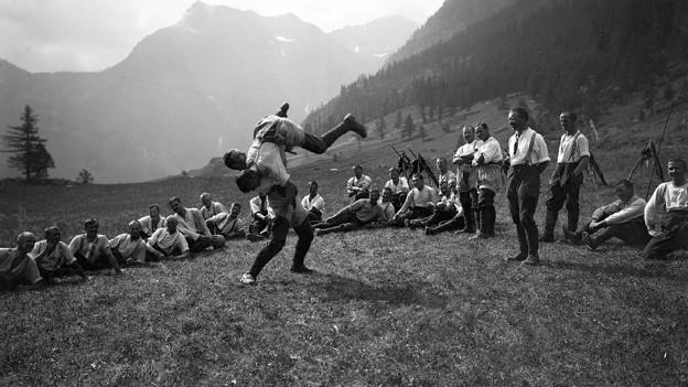 Schwarz-Weiss Fotografie mit einer Gruppe von Männern, die in Schwingerhosen auf einer Bergwiese sitzen und zwei anderen beim Kampf zusehen.