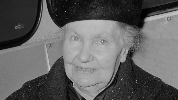 Schwarz-Weiss Fotografie von Gertrud Kurz mit Hut und Mantel.