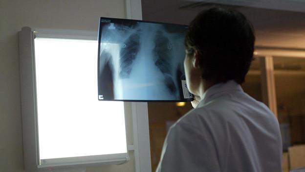 Ein Arzt studiert eine Röntgenaufnahme (Symbolbild).