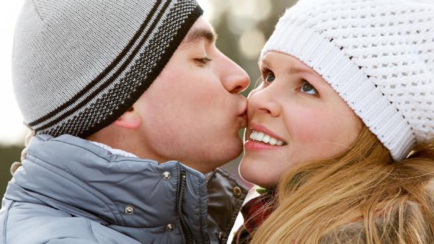 Eine junge Frau gibt einem jungen Mann einen Kuss auf die Wange.