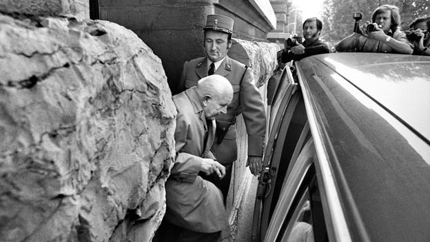 Auf der Schwarz-Weiss Fotografie verlässt der verurteilte Jean-Louis Jeanmaire das Gerichtsgebäude und steigt in ein Auto.