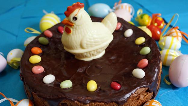 Eine mit Schokolade überzogene und mit Zuckereiern und einem weissen Schokoladenhuhn dekorierte Torte.