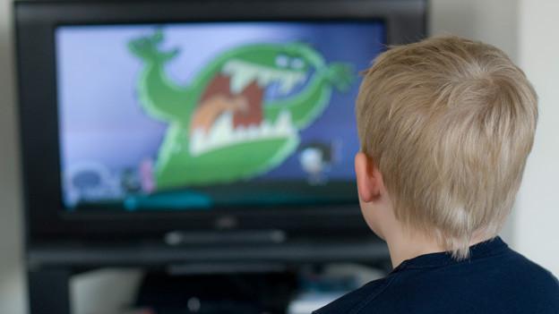 Ein Bub sitzt vor dem Fernseher auf dessen Bildschirm ein grünes Phantasietier sein grosses Maul aufreisst.