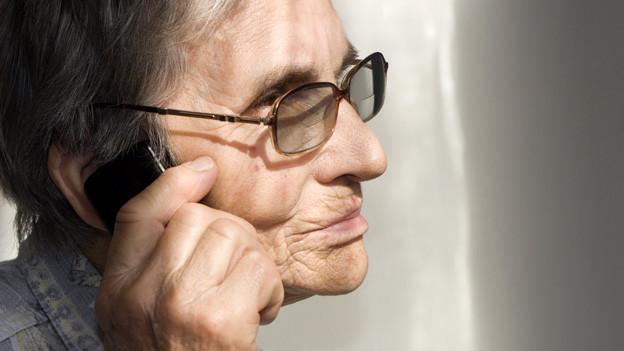 Eine alte Frau beim Telefonieren.