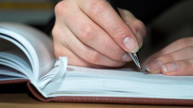 Hand einer Frau, die einen Eintrag in ein aufgeschlagenes Buch schreibt.
