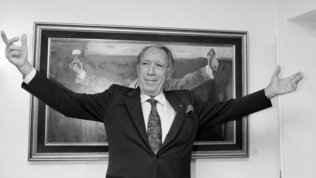 Der Schauspieler steht mit dem Rücken zur Wand vor einem Gemälde und breitet seine Arme weit aus.