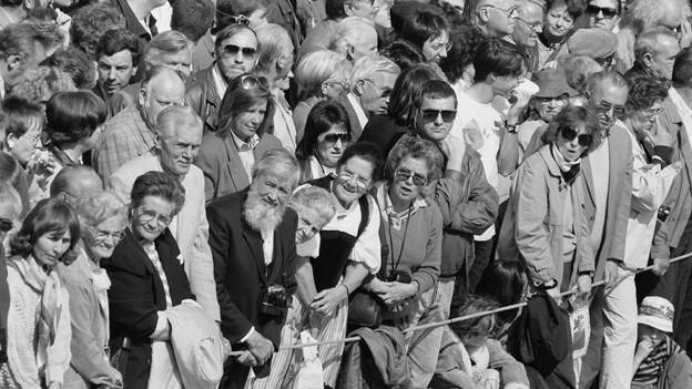 Schwarz-Weiss Fotografie mit vielen Menschen, die hinter einem gespannten Seil stehen.