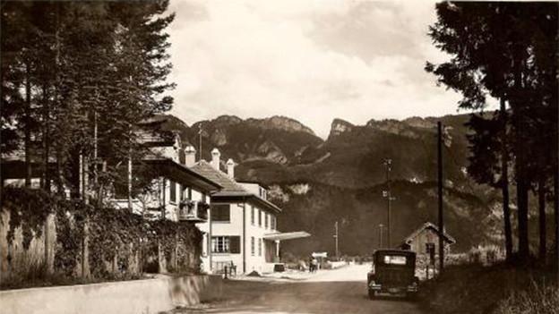 Alte Fotografie mit einem Auto am Strassenrand vis-à-vis von Häusern.