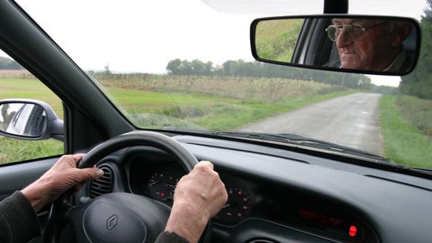Ein älterer Mann fährt Auto, sein Gesicht ist im Rückspiegel zu sehen.