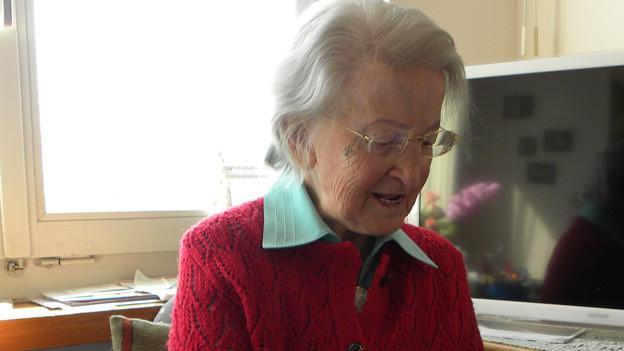 Die Seniorin sitzt in ihrer Wohnun an einem Tisch und blättert in einer Zeitschrift.