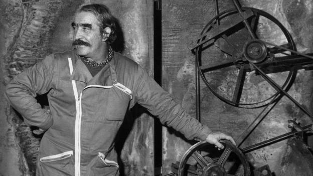 Schwarz-Weiss Fotografie mit dem Künstler, der neben einer Eisenplastik steht.