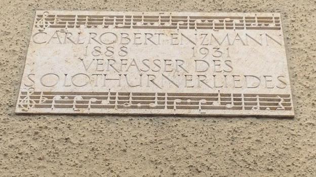 In Stein gemeisselte Inschrift: Carl Robert Enzmann, Verfasser des Solothurnerliedes.