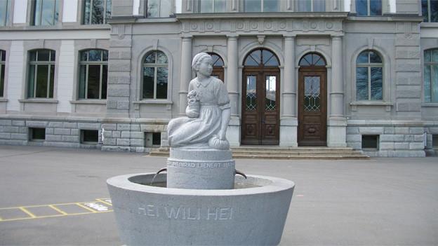 Die Skulptur eines Mädchens auf einem Brunnen, der vor dem Platz einer Schule steht.