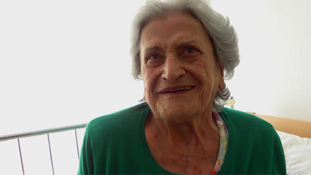 Die Seniorin trägt eine grüne Strickjacke und sitzt auf ihrem Bett.