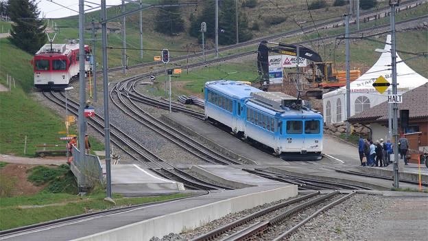 Ein roter Zug fährt talwärts, ein blauer Zug bergwärts.