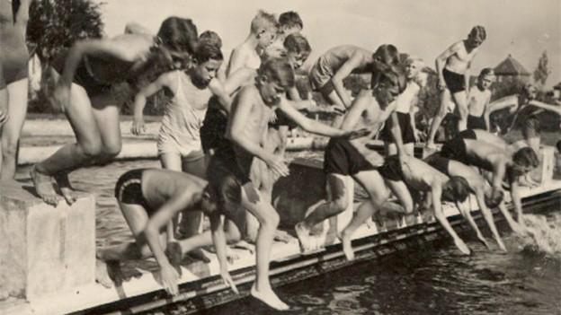 Alte Fotografie mit Buben und Mädchen, die ins Wasser springen.