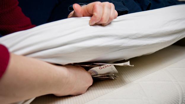 Eine Frau legt ein Bündel Geldscheine unter die Matratze.