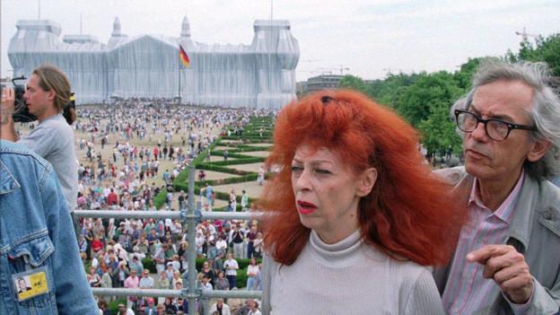 Im Hintergrund sieht man den in Stoff verhüllten Reichstag, davor zahlreiches Publikum und ganz im Vordergrund das Künstlerehepaar Jeanne-Claude und Christo.