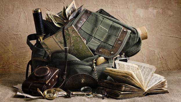 Ein alter Rucksack und viele verschiedene Wanderutensilien.