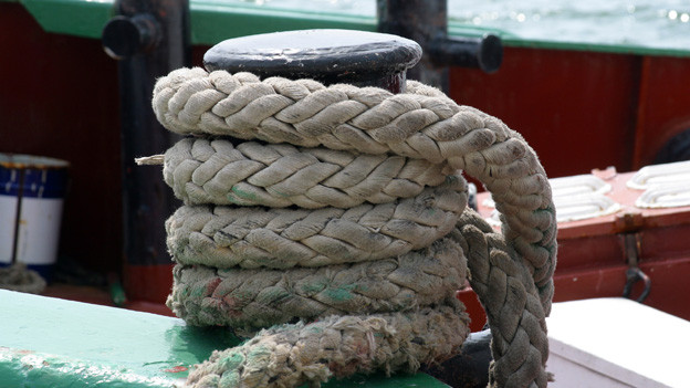 Ein langes dickes Seil auf einem Schiff.