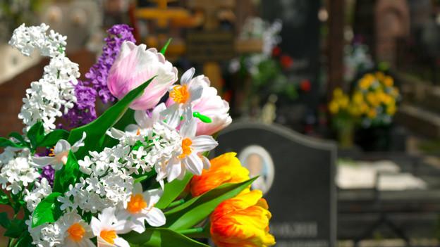 Ein bunter Blumenstrauss auf einem Grab.