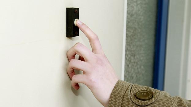 Finger einer Männerhand auf einer Türklingel.