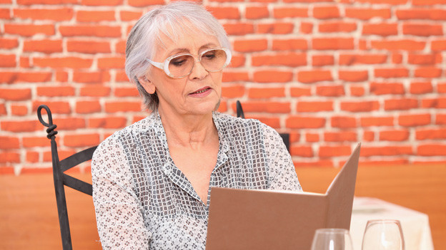 Eine ältere Frau mit grauen Haaren sitzt im Restaurant alleine an einem Tisch und studiert die Menukarte.