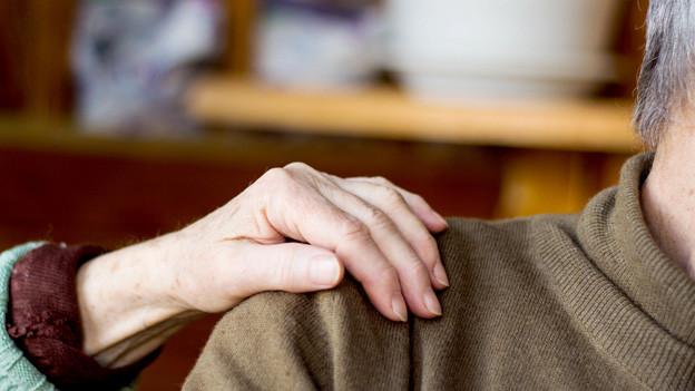 Eine Frauenhand auf der Schulter eines Mannes.