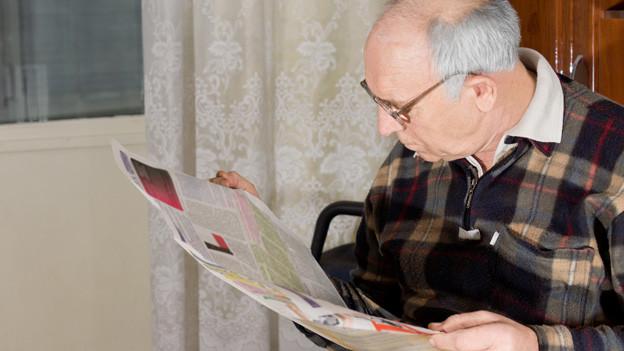 Ein älterer Mann liest versunken in der Zeitung.
