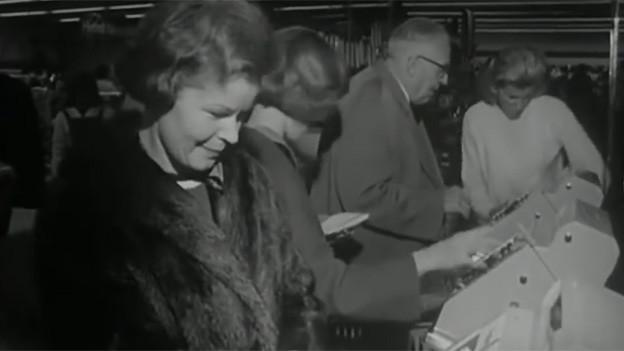 Filmausschnitt in schwarz-weiss mit Frauen und Männern, die vor Kassen stehen.