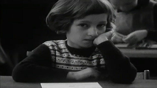 Filmausschnitt in schwarz-weiss von einer Erstklässlerin, die in der Schulbank sitzt.