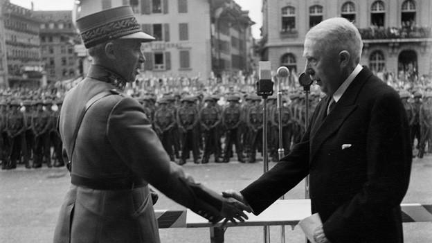 Schwarz-Weiss Fotografie mit General und Bundesrat, die sich auf dem Bundesplatz die Hände schütteln.
