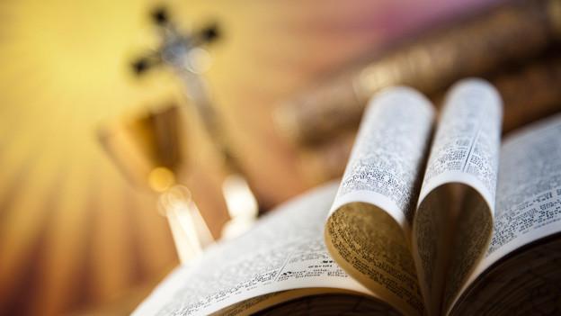Eine aufgeschlagene Bibel liegt auf einem Altar vor einem Kreuz.