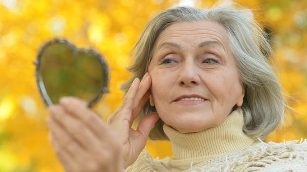 Eine ältere Frau hält einen herzförmigen kleinen Spiegel in der Hand und begutachtet ihr Spiegelbild.