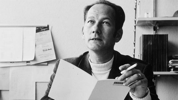 Schwarz-Weiss Fotografie mit Ueli Beck in seinem Büro im Radiostudio. In einer Hand hält er eine Broschüre, in der anderen eine Zigarette.